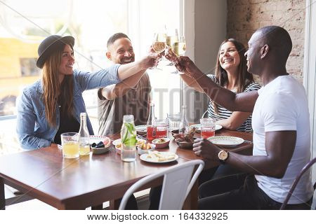 Young Group Of Smiling Friends Clinking Glasses