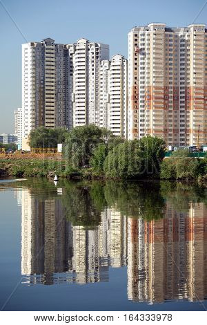 Cityscape with many new constructed block of flats after river over clear blue cloudless sky in summer day