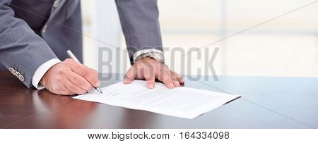 Businessman Signing An Official Document In His Office