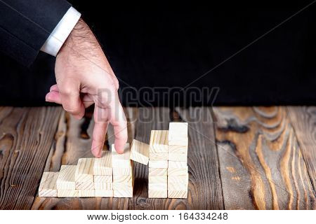 Businessman Walking Up Trappy Staircase Of Wooden Blocks To Success Career In Business Concept