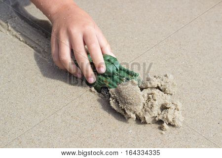 Hand of little child playing with sand