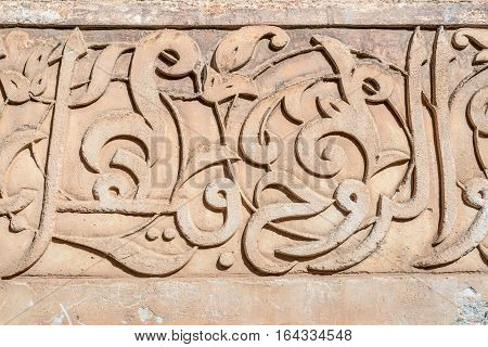 Islamic Calligraphy Marrakesh Morroco. Sacred Islamic calligraphy is carved into the walls of the Ben Youssef madrasa a traditional Islamic college in the central medina area of Marrakesh.