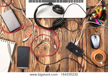 Untidy Working Desk With Various Cables In Office Top View