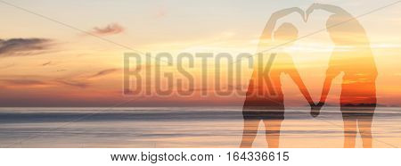 Double exposure of couple make a heart shape with her body over sea background with twilight