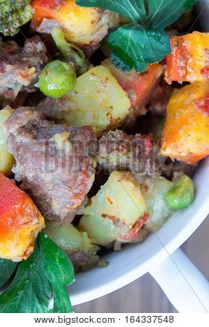 Beef meat stewed with potatoes, carrots and spices in ceramic pot on wooden background. macro