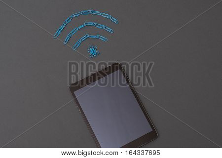 Wireless Signal Symbol Made Of Paperclips And Digital Tablet