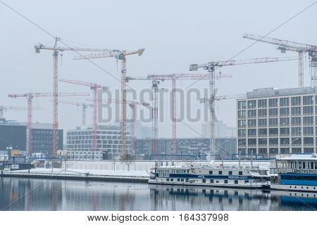 Berlin Germany - January 8 2017: Construction cranes at river spree in Berlin near the Mercedes Benz arena.