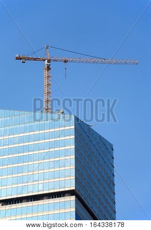 Yellow hoisting tower crane on top of construction skyscraper building over blue sky. Vertical photo