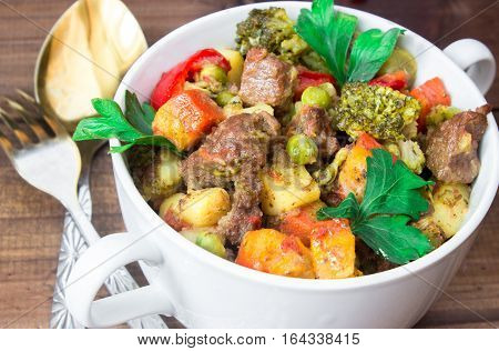 closeup beef meat stewed with potatoes, carrots and spices in ceramic pot on wooden background