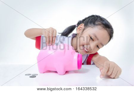 Asian little girl in Thai student uniform putting coins to piggy bank selective focus on hand shallow depth of field