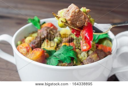 closeup beef meat stewed with potatoes, carrots and spices in ceramic pot with a piece on a fork on wooden background