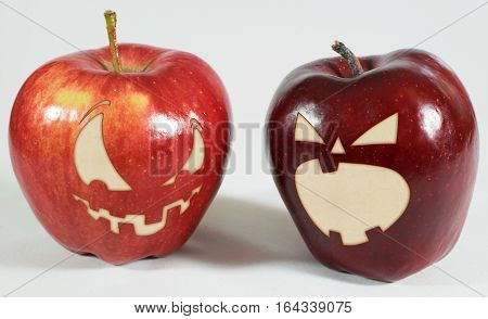 2 red apples with creepy carved faces on a white background