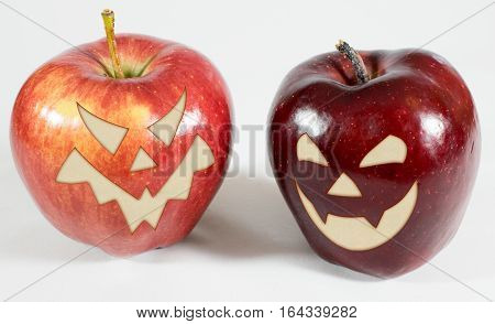 2 red apples with funny carved faces on a white background