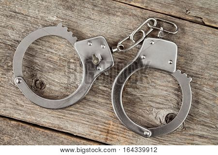 Top view of handcuffs on the wooden background