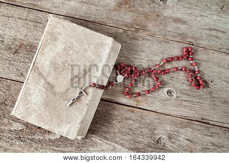Very old prayer book and rosary on wooden background