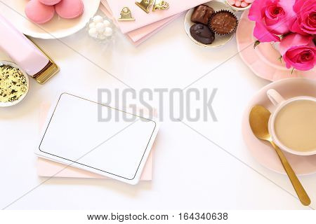 Bright pink and gold desktop with romantic touches and office supplies.