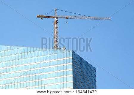 Yellow hoisting tower crane on top of construction skyscraper building over blue sky