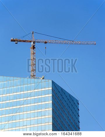 Yellow hoisting tower crane on top of construction skyscraper building over clear blue sky. Vertical photo