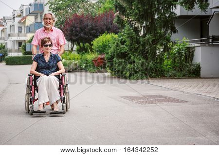 Senior couple in wheelchair, enjoying a day in the city