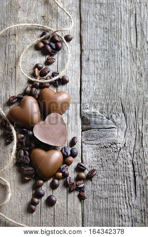 Chocolate heart and coffee beans on wooden background. Happy Valentine's Day.