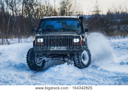 Lviv Ukraine - December 04 2016: Unknown racers on off-road vehicle Jeep Cherokee overcomes the track at amateur competitions among off-road vehicles near ringroad of the city Lviv Ukraine