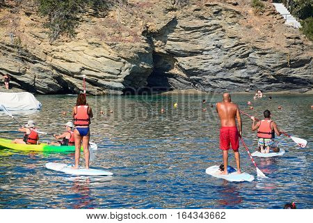 BALI, CRETE - SEPTEMBER 16, 2016 - Holidaymakers on paddle boards with a small beach and cave to the rear Bali Crete Greece Europe, September 16, 2016.