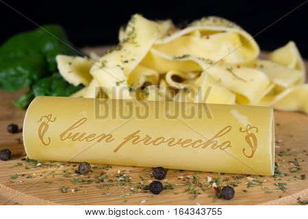 On a wooden board is in the foreground a cannelloni with the lettering - enjoy your meal - in spanish words in the background are further noodles garnished with leaf spinach and pepper grains