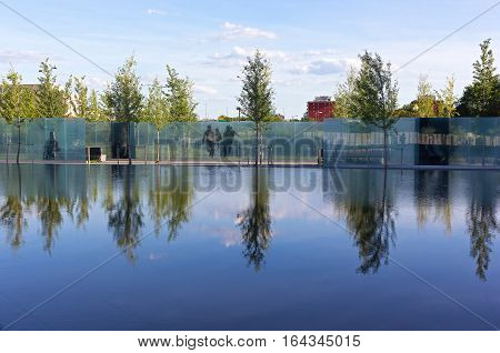 WASHINGTON DC USA - AUGUST 7: American Veterans Disabled for Life Memorial dedicated to wounded in combat on August 7 2016 in Washington DC. Reflection pool and young trees create a calming effect.