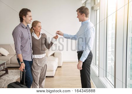 Young attractive married couple in love buying or renting new apartment, meeting with real estate agent, occupiers moving into rented accommodation, starting family life, moving out from another city