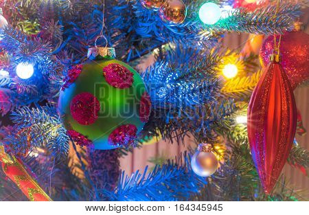 Christmas tree decorations.  Green, matte finish, orb with magenta circles, glows, surrounded by vivid blue and multicolored mini-lights close up on a small faux indoor Christmas tree.