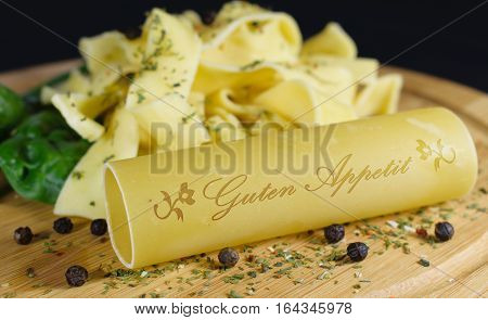 On a wooden board is in the foreground a cannelloni with the lettering - bon appetite - in german words in the background are further noodles garnished with leaf spinach and pepper grains