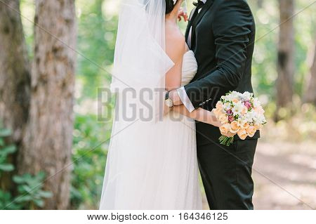 Bouquet from spring flowers. Wedding bouquet. Bride holds wedding bouquet. The groom embraces the bride.