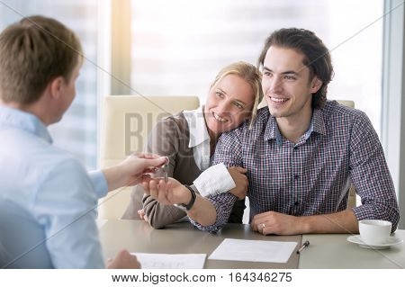 Young happy couple in love getting a key for own apartment, left the parental home, access their own rented tenancy, first home-buying experience, decided mortgage terms