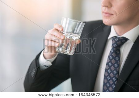 Close up of a businessman hand holding a glass with pure water, dehydration, drink enough liquids throughout the day, feeling thirsty, experiencing a headache