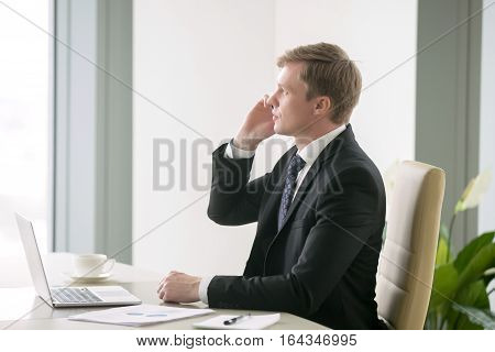 Young handsome businessman working with laptop at the desk in modern office, talking on phone, looking at the window, setting up a meeting, planning and organizing, providing great customer service