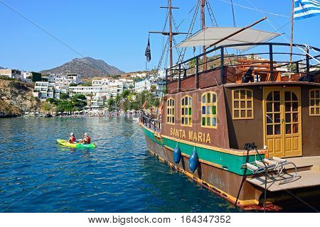 BALI, CRETE - SEPTEMBER 16, 2016 - Santa Maria Galleon ship in the harbour with a couple canoeing and tourists relaxing on the beach to the rear Bali Crete Greece Europe, September 16, 2016.