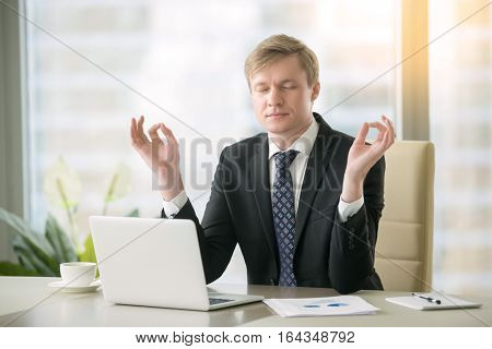 Young calm businessman working with laptop in yoga pose at modern office desk, minimize day discomfort, focusing on work, boost of energy after important task, keep feeling focused before meeting