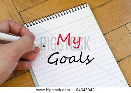 Human hand over wooden background and my goals text concept