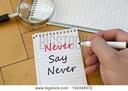 Human hand over wooden background and never say never text concept
