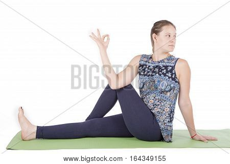 Sporty beautiful young woman in white sportswear practicing yoga, sitting in twisted pose, Vakrasana. top doing marichiasana III, twist pose at white background. Free space for text