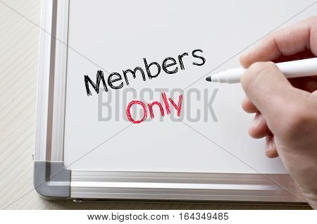 Human hand writing members only on whiteboard