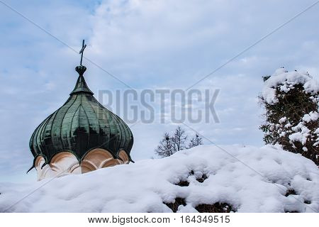 The dome of an Eastern orthodox church visible behind a snowy fence