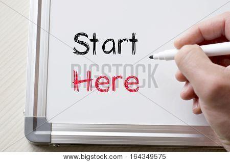 Human hand writing start here on whiteboard