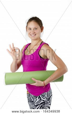 Sports girl with mat for sports in the hands on a white background. It shows hand sign ok