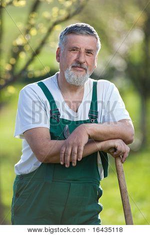 Portrait of a handsome senior gardener in a garden