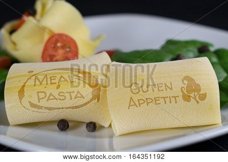 On a white plate are 2 noodles with the lettering