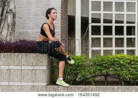 Young fitness woman having rest after running in city. Tired sporty girl sitting and listening to music in headphones outside.