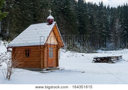 A small church in the snow is in the forest of the Carpathians around the centuries-old pine trees covered with snow. Mountain Dragobrat western Ukraine.
