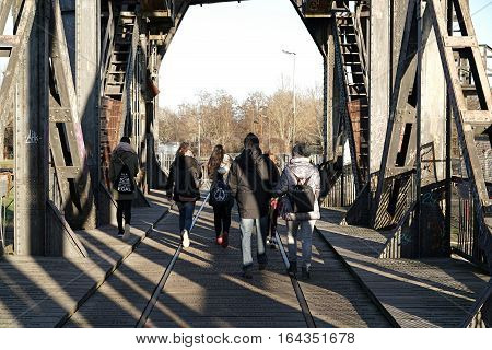 MAGDEBURG, GERMANY - DECEMBER 29, 2016: Pedestrians cross the Lift Bridge in Magdeburg to the other bank of the river Elbe. The dilapidated bridge is often used by pedestrians to go to the other side of the Elbe