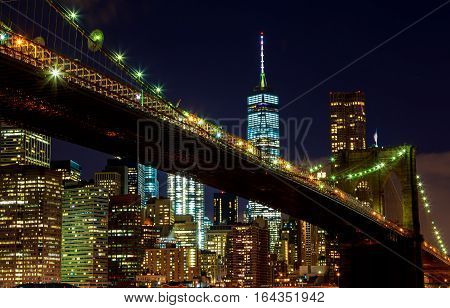 Brooklyn Bridge closeup over East River at night in New York City Manhattan with lights